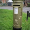 Gold-painted pillar box in Station Road in honour of Peter Charles' Olympic gold medal in the Equestrian section