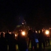 The torchlight procession gathering around the bonfire