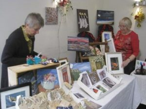 Chris and Sue arranging their paintings and cards from the Beech Art Group